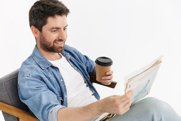 Portret przystojnego brodatego mężczyzny w zwykłych ubraniach, siedzącego na krześle na białym tle, czytającego gazetę, pijącego kawę