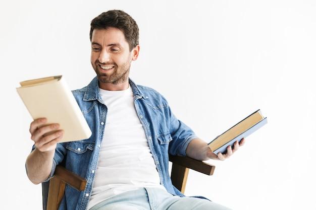 Portret przystojnego brodatego mężczyzny w zwykłych ubraniach, siedzącego na krześle na białym tle nad białą ścianą, trzymającego książki