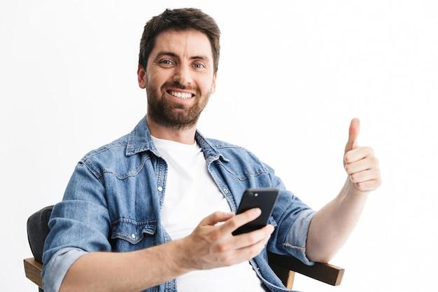 Portret przystojnego brodatego mężczyzny w zwykłych ubraniach, siedzącego na krześle na białym tle nad białą ścianą, trzymającego telefon komórkowy
