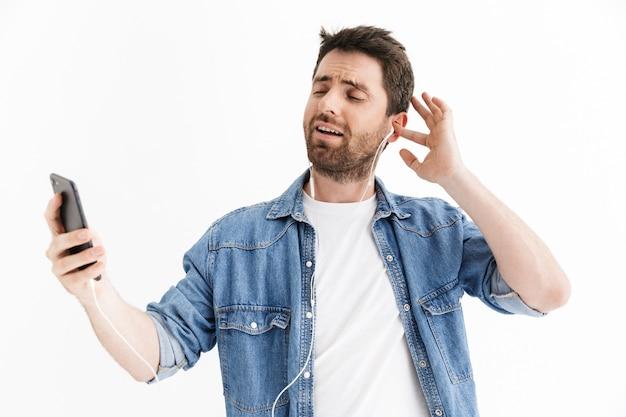 Portret przystojnego brodatego mężczyzny w zwykłych ubraniach, stojącego na białym tle, słuchającego muzyki przez słuchawki, trzymającego telefon komórkowy