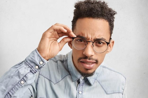 Portret przystojnego brodatego studenta nerda nosi okrągłe okulary, patrzy uważnie
