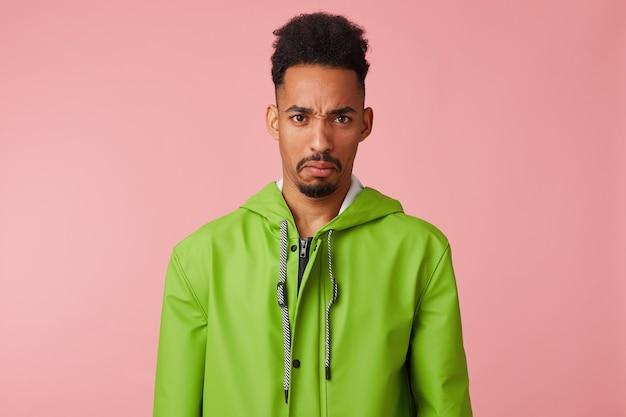 Portret przystojnego ciemnoskórego faceta marszczy brwi z niezadowoleniem, nie lubi pomysłu na obiad, ubrany w zielony płaszcz przeciwdeszczowy, odizolowany.