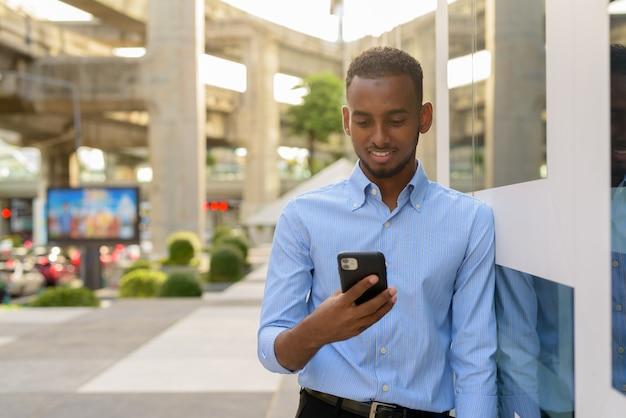 Portret przystojnego czarnego afrykańskiego biznesmena na zewnątrz w mieście latem przy użyciu telefonu komórkowego, patrząc na szczęśliwego