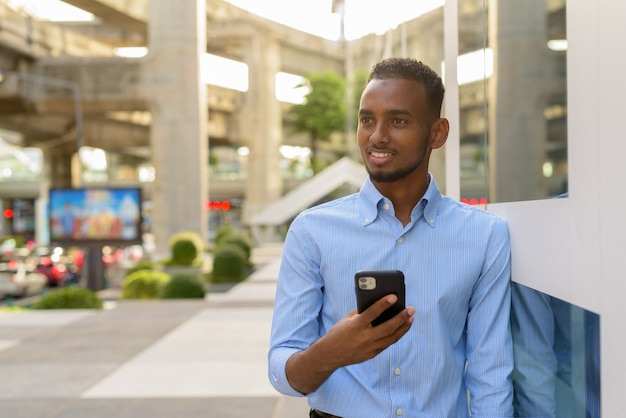 Portret przystojnego czarnego afrykańskiego biznesmena na zewnątrz w mieście latem przy użyciu telefonu komórkowego podczas uśmiechania się i myślenia