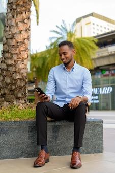 Portret przystojnego czarnego afrykańskiego biznesmena na zewnątrz w mieście latem przy użyciu telefonu komórkowego podczas uśmiechania się w pionie