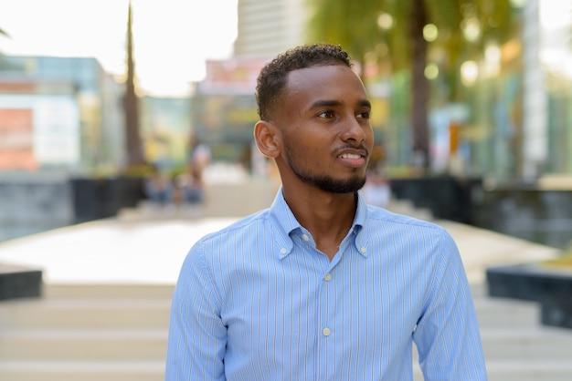 Portret przystojnego czarnego afrykańskiego biznesmena na zewnątrz w mieście latem, uśmiechając się i myśląc poziomo
