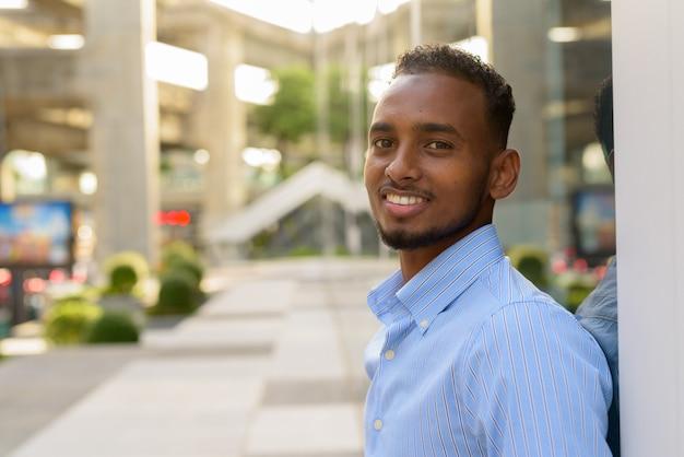 Portret przystojnego czarnego afrykańskiego biznesmena na zewnątrz w mieście latem, uśmiechając się i patrząc na kamerę