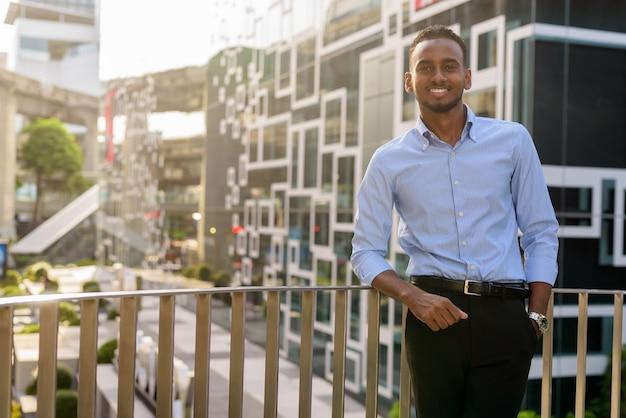 Portret przystojnego czarnego afrykańskiego biznesmena na zewnątrz w mieście latem