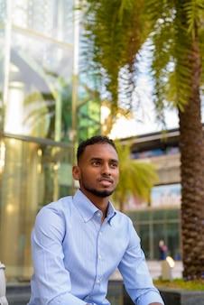 Portret przystojnego czarnego afrykańskiego biznesmena na zewnątrz w mieście podczas letniego siedzenia i myślenia w pionie