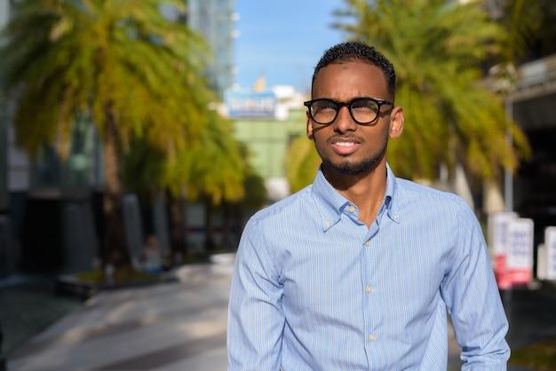 Portret przystojnego czarnego afrykańskiego biznesmena na zewnątrz w mieście podczas letniego ujęcia poziomego