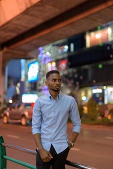 Portret przystojnego czarnego afrykańskiego biznesmena na zewnątrz w mieście w nocy myślącego pionowego strzału