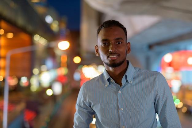 Portret przystojnego czarnego afrykańskiego biznesmena na zewnątrz w mieście w nocy, uśmiechając się i patrząc na poziome ujęcie kamery