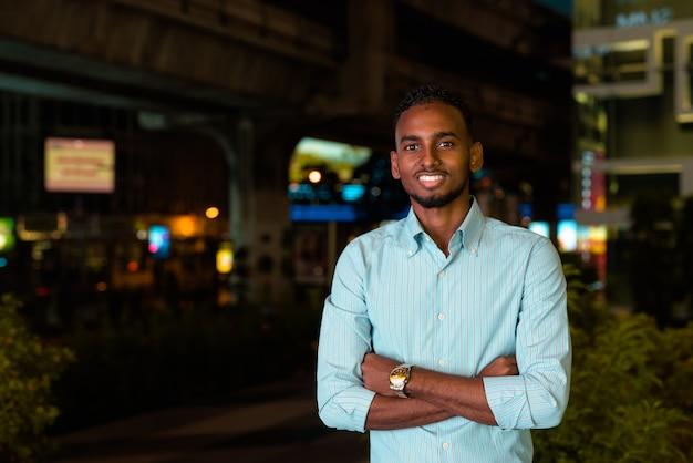 Portret przystojnego czarnego afrykańskiego biznesmena na zewnątrz w mieście w nocy uśmiechającego się z rękami skrzyżowanymi i patrzącego na poziome ujęcie kamery
