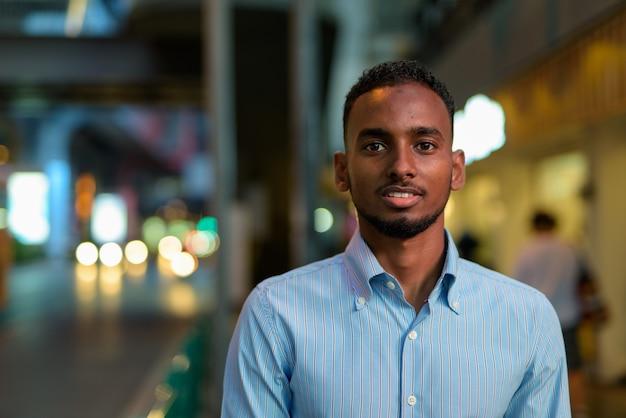 Portret przystojnego czarnego afrykańskiego biznesmena na zewnątrz w mieście w nocy uśmiechający się poziomy strzał