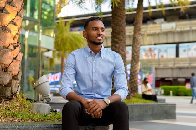 Portret przystojnego czarnego afrykańskiego biznesmena siedzącego i uśmiechającego się, myśląc na zewnątrz w mieście podczas letniego ujęcia poziomego