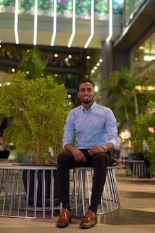 Portret przystojnego czarnego afrykańskiego biznesmena siedzącego na zewnątrz w mieście w nocy, podczas gdy się uśmiecha