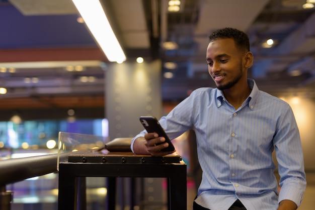 Portret przystojnego czarnego afrykańskiego biznesmena siedzącego w centrum handlowym podczas uśmiechania się i korzystania z poziomego ujęcia telefonu komórkowego phone
