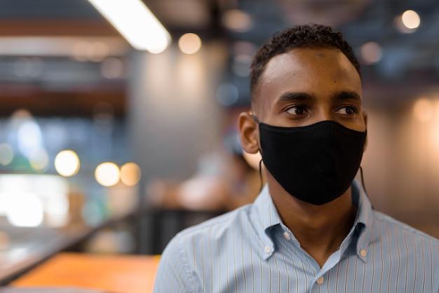 Portret przystojnego czarnego afrykańskiego biznesmena w centrum handlowym noszącego maskę na twarz, myśląc o poziomym ujęciu