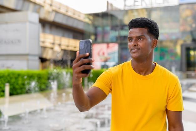 Portret przystojnego czarnego afrykańskiego mężczyzny noszącego żółtą koszulkę na zewnątrz w mieście latem obok fontanny podczas korzystania z telefonu komórkowego