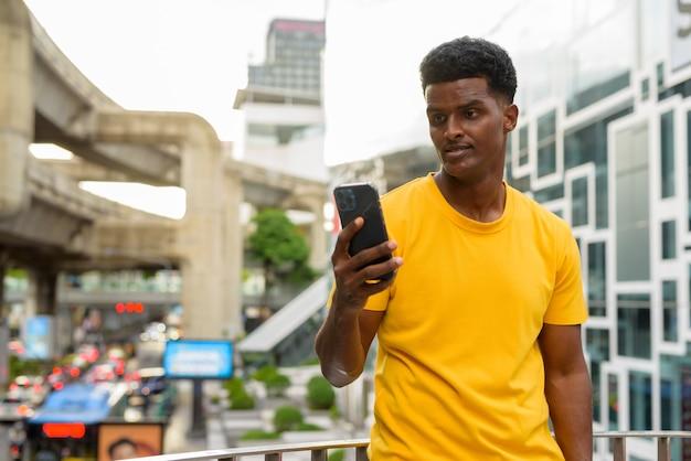 Portret przystojnego czarnego afrykańskiego mężczyzny noszącego żółtą koszulkę na zewnątrz w mieście latem podczas korzystania z telefonu komórkowego