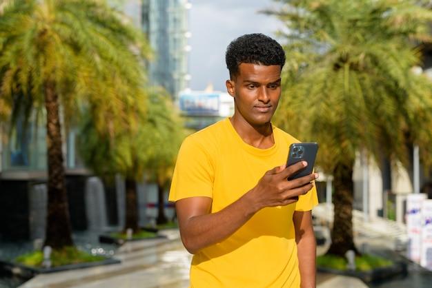 Portret przystojnego czarnego afrykańskiego mężczyzny noszącego żółtą koszulkę na zewnątrz w mieście latem przy użyciu telefonu komórkowego