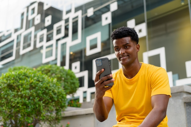 Portret przystojnego czarnego afrykańskiego mężczyzny noszącego żółtą koszulkę na zewnątrz w mieście podczas korzystania z telefonu komórkowego