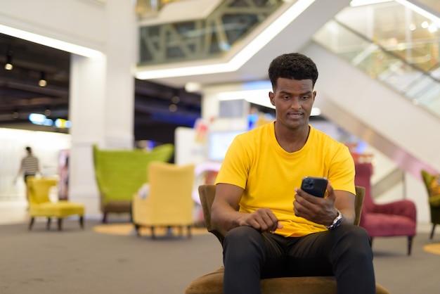 Portret przystojnego czarnego afrykańskiego mężczyzny noszącego żółtą koszulkę podczas siedzenia i korzystania z telefonu komórkowego