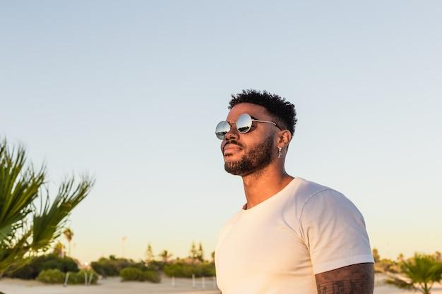 Portret przystojnego czarnego amerykanina noszącego okulary przeciwsłoneczne podczas zachodu słońca na plaży