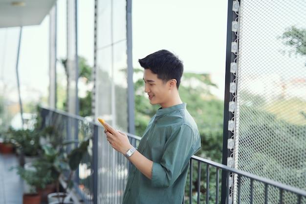 Portret przystojnego faceta używającego swojego telefonu komórkowego
