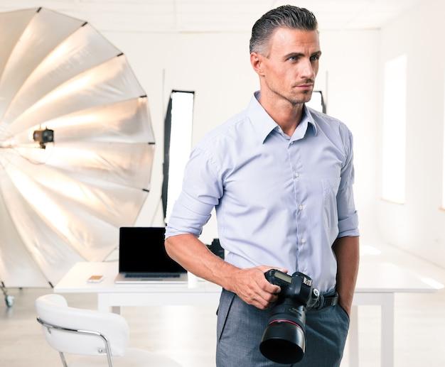 Portret przystojnego fotografa stojącego z aparatem w studio