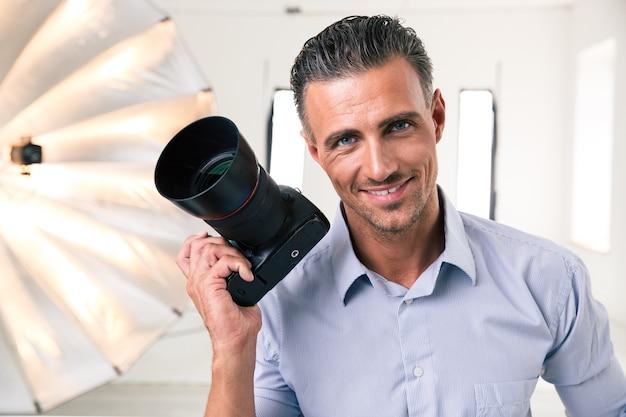 Portret przystojnego fotografa trzymającego aparat w studio