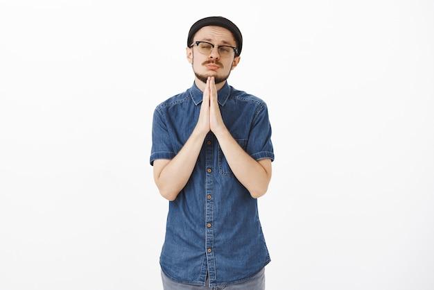 Portret przystojnego i wzruszającego przystojnego brodatego mężczyzny w okularach i modnej czarnej czapce trzymającej się za ręce w modlitwie w pobliżu brody, mrużąc oczy i przechylając głowę, prosząc o przebaczenie lub przysługę
