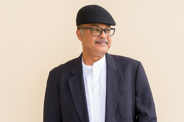Portret przystojnego indyjskiego biznesmena z wąsami w kapeluszu na tle zwykłej ściany