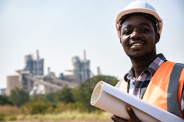 Portret przystojnego inżyniera mężczyzny trzymającego papierkową robotę przed fabryką przemysłu naftowego