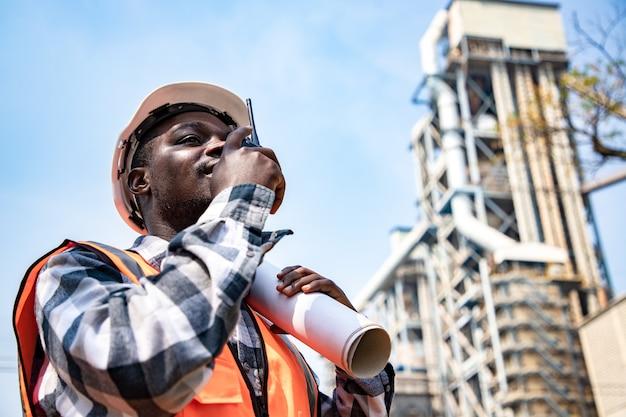 Portret przystojnego inżyniera używającego walkie talkie i trzymającego papierkową robotę w fabryce przemysłowej