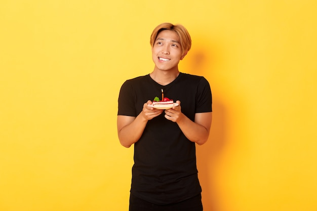 Portret przystojnego marzycielskiego azjatyckiego faceta patrzącego w lewym górnym rogu i myślącego, życząc sobie, świętując urodziny i trzymając tort urodzinowy, żółta ściana
