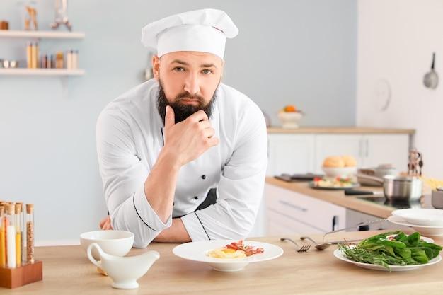 Portret przystojnego męskiego szefa kuchni w kuchni