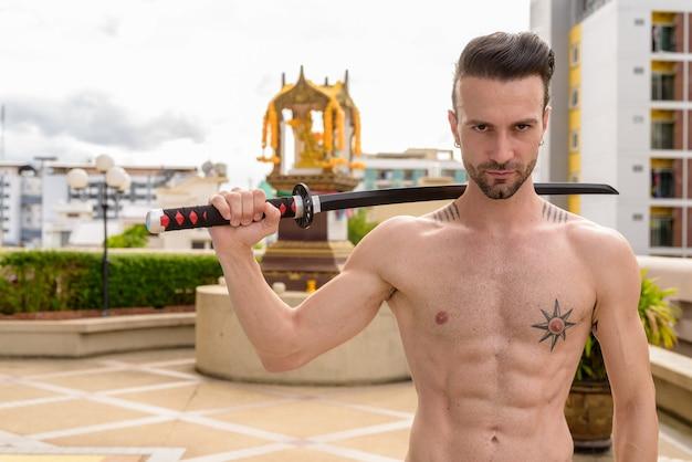 Portret przystojnego mężczyzny bez koszuli na zewnątrz trzymającego miecz