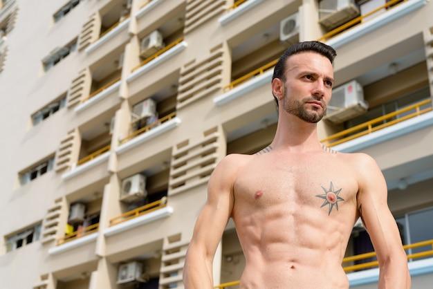 Portret przystojnego mężczyzny bez koszuli na zewnątrz z sześciopakiem abs i tatuażami