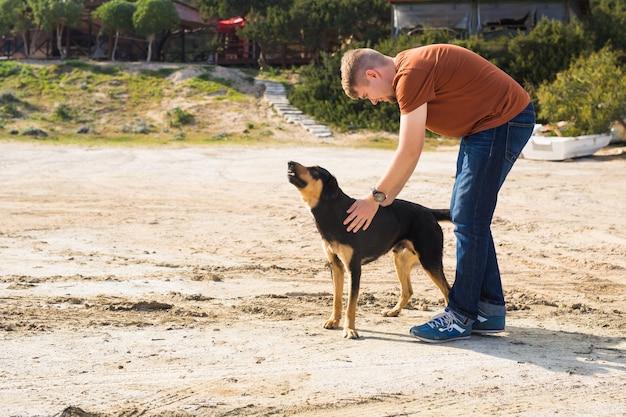 Portret przystojnego mężczyzny i psa w parku