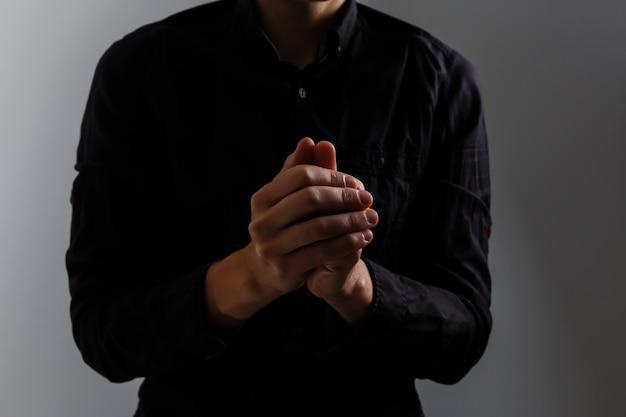 Portret przystojnego mężczyzny modlącego się na szarym tle