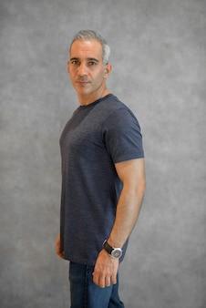 Portret przystojnego mężczyzny stojącego przed szarą ścianą pionowego strzału
