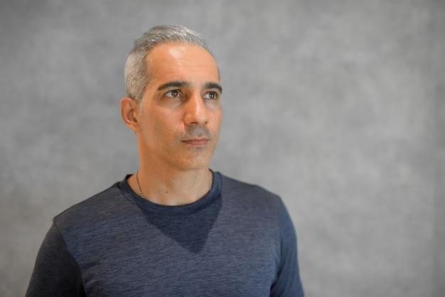 Portret przystojnego mężczyzny stojącego przed szarą ścianą poziomego strzału podczas myślenia