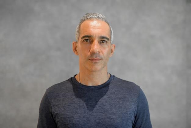 Portret przystojnego mężczyzny stojącego przed szarą ścianą poziomego strzału