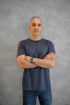 Portret przystojnego mężczyzny stojącego przy szarej ścianie ze skrzyżowanymi rękami