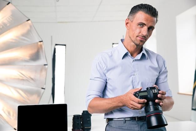 Portret przystojnego mężczyzny trzymającego aparat w studio