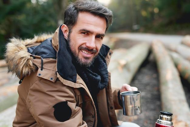 Portret przystojnego mężczyzny w lesie w okresie zimowym
