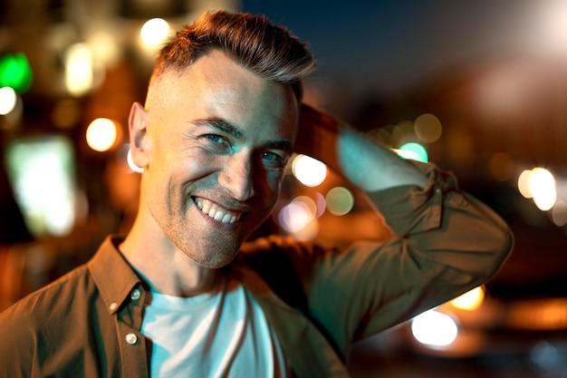 Portret przystojnego mężczyzny w nocy w światłach miasta