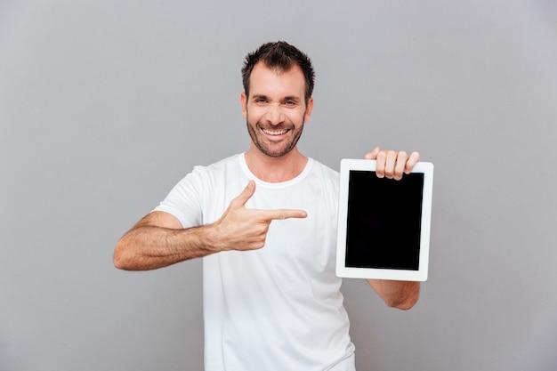 Portret przystojnego mężczyzny wskazującego palcem na pustym ekranie komputera typu tablet na białym tle na szarym tle