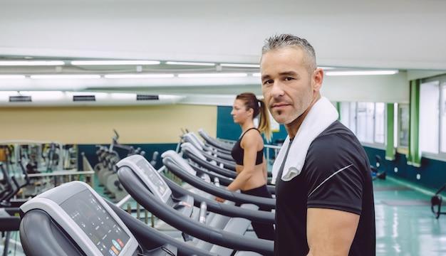 Portret przystojnego mężczyzny z ręcznikiem na szyi podczas treningu na bieżni w centrum fitness fitness